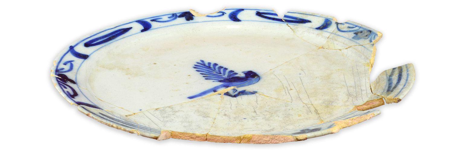 AssietteMCC/LRAQ, photo: Aurélie DesgensCour intérieure de la maison Dumont. Vers 1700-1750Faïence blanche, Delft, Hollande. Décor peint en camaïeu de bleu à l'intérieur. Au centre, un perroquet surune branche. Ce type d'assiette a fait la renommée des artisans de Delft dès la décennie de 1690. Toutefois, il parvient en Nouvelle-France après 1714, à la fin de la guerre de Succession d'Espagne.