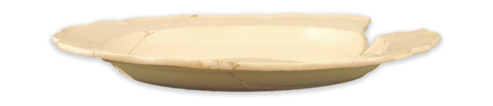 AssietteMCC/LRAQ, photo : Catherine CaronLatrines de la maison Guillaume-Estèbe. Vers 1753-1800Terre cuite fine de type creamware à décor royal, Angleterre. Dans la seconde moitié du 18e siècle, sous l'influence de la nouvelle métropole britannique, les porcelaines d'importation chinoise côtoient de nouvelles vaisselles de terre cuite finesur les tables bourgeoises de Place-Royale : la mode est désormais au creamware.Dès 1765, les navires anglais acheminent vers le port de Québec ces vaisselles produites en série grâce au procédé de moulage. Elles sont ensuite distribuées à Trois-Rivières et à Montréal.